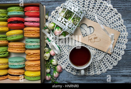 Macaroons in the box with decorations and a cup of tea - Stock Photo