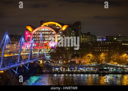 Night view across the River Thames to the illuminated Golden Jubilee Bridge and Charing Cross Station, London - Stock Photo