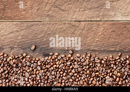 Overhead shot looking down on a flatlay image of coffee beans over a rustic wood table top background with copy - Stock Photo