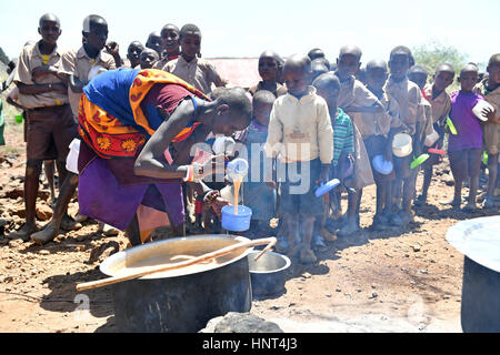 Kajiado, Kenya. 16th February, 2017. Students wait in line for their lunch, porridge cooked with government aid - Stock Photo