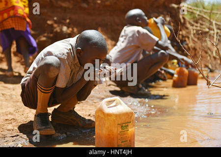 Kajiado, Kenya. 16th February, 2017. A young boy fetches water to drink with his hands at Olomayiana West, Kajiado - Stock Photo