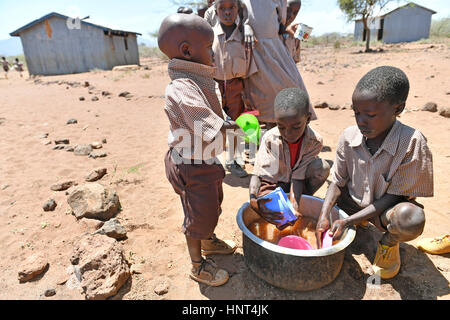 Kajiado, Kenya. 16th February, 2017. Students wash the dishes after lunch in line at Olomayiana West Primary School - Stock Photo