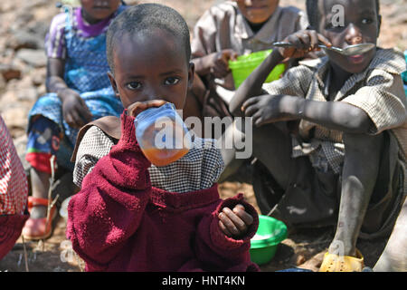 Kajiado, Kenya. 16th February, 2017. A girl drinks water during lunch hour at Olomayiana West Primary School in - Stock Photo