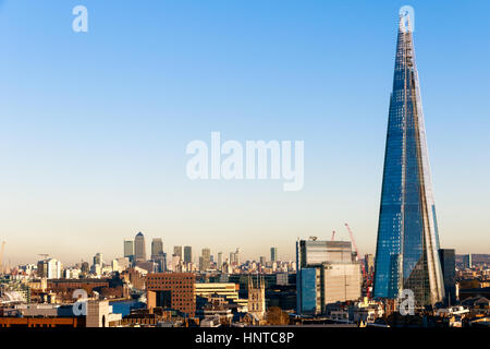 Financial district cityscape of London, including Canary Wharf and The Shard against a blue cloudless sky - Stock Photo