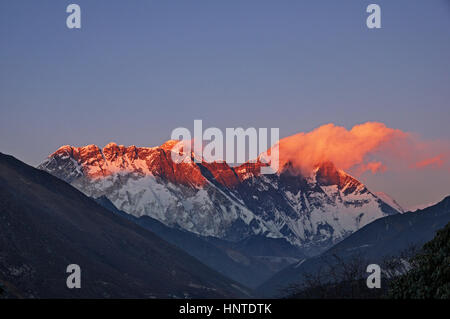 last light on Mount Everest Nuptse and Lhotse with a few clouds viewed from Tengboche - Stock Photo