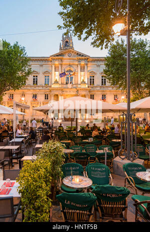 Cafes and restaurants in the early evening overlooked by the Hotel de Ville in Place de l'Horloge, Avignon, France - Stock Photo