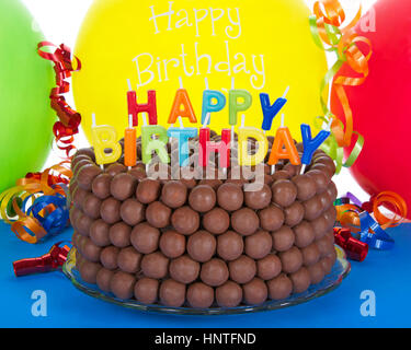 Whopper of a Chocolate Birthday Cake decorated with candy malt balls and Happy Birthday Candles. Balloon background. - Stock Photo