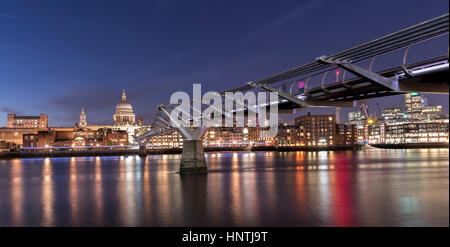 Night time view of the Millennium Bridge and River Thames, London, UK, with St Paul's Cathedral, lit up on the opposite - Stock Photo