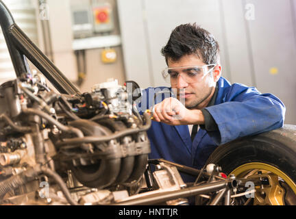 Mechanic working on a car engine - Stock Photo