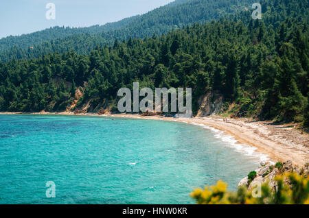 Hidden wild beach with sand against the green forest of the pine trees in Vourvourou, Sithonia, Greece. View from - Stock Photo