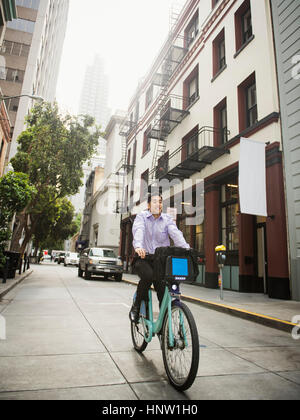 Chinese businessman commuting on bicycle in city - Stock Photo
