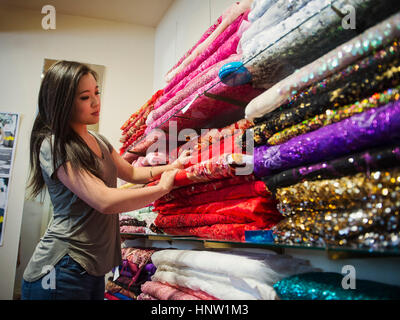 Chinese woman shopping for fabric in store - Stock Photo