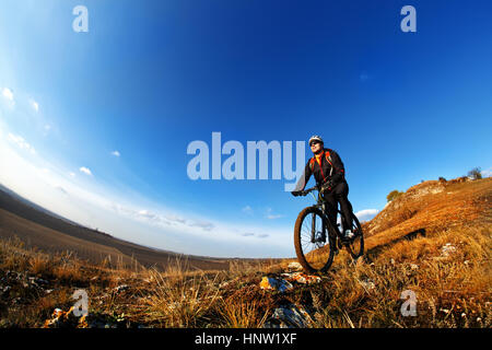 Low, wide angle portrait against blue sky of mountain biker going downhill. Cyclist in black sport equipment and - Stock Photo