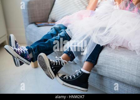 Legs of girls wearing tutus on sofa - Stock Photo