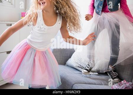 Girls wearing tutus dancing on sofa - Stock Photo