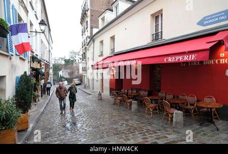 Montmartre, Paris. two people walk along a cobbled street in Montmartre Village,  Paris - Stock Photo