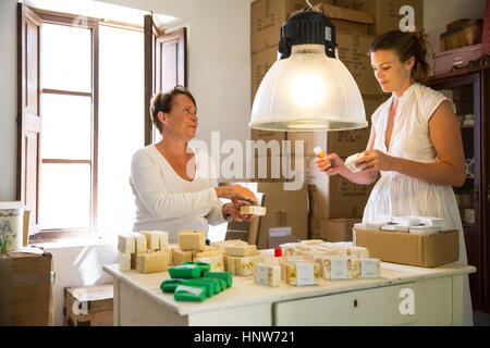 Two women packing soap products in handmade soap workshop - Stock Photo