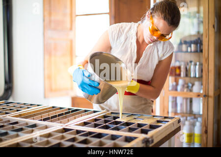 Young woman pouring liquid into soap mould in handmade soap workshop - Stock Photo