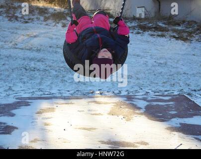 A little girl outside on a tire swing in winter. - Stock Photo