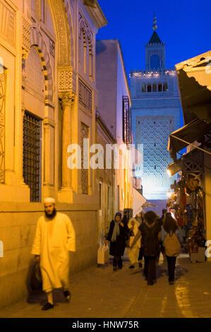 Tunisia: City of Tunis.Medina. Rue Sidi Ben Arous, in background minaret of  Ez- Zitouna Mosque (Great Mosque) - Stock Photo