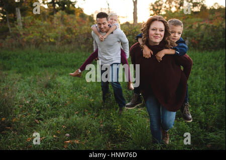 Parents giving children piggy back in field - Stock Photo