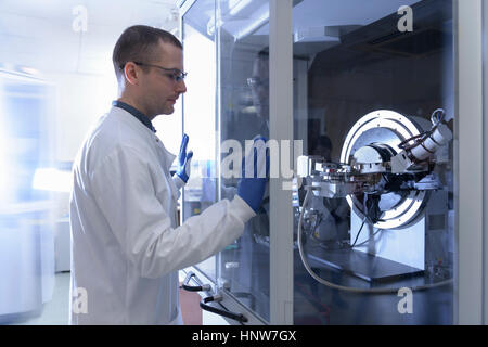 Scientist operating crystal x-ray diffraction machine in crystal engineering research laboratory - Stock Photo