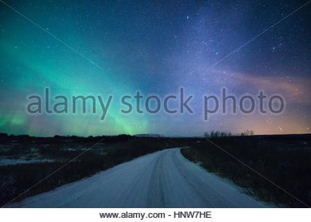 Road under aurora borealis at night, Thingvellir, Iceland - Stock Photo