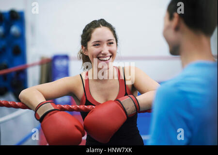 Young female boxer leaning on boxing ring ropes chatting - Stock Photo
