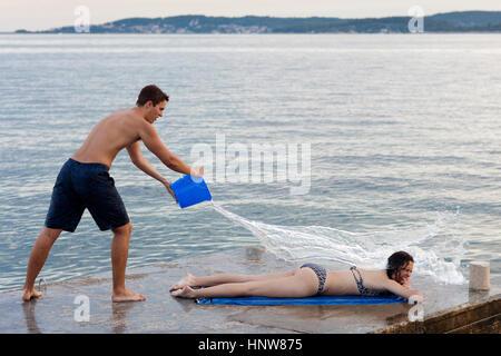 Young man throwing bucket of water over female sunbather, Orebic, Croatia - Stock Photo