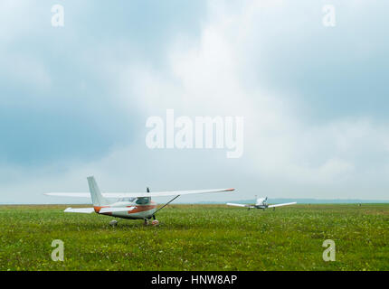 Two light aircraft flying parked on airfield - Stock Photo