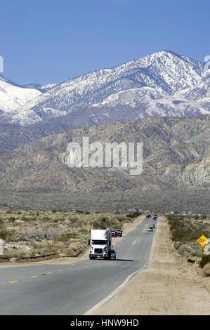 Truck on road in the Palm Desert with mountains with snow near Palm Springs, CA - Stock Photo