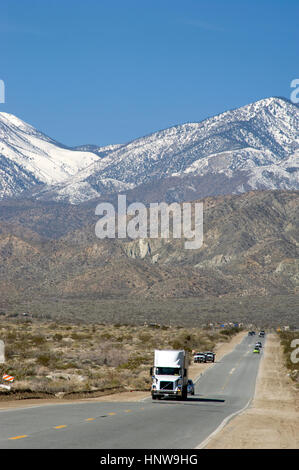Truck on road in the Palm Desert with mountains with snow near Palm Springs - Stock Photo