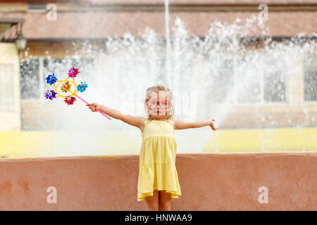 Nice little girl holding a pinwheel in hand. A walk in the summer park near the city fountain. Summer vacation. - Stock Photo
