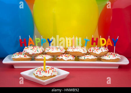 Miniature donut cake on long white plate with happy birthday candles one donut on single square plate with single - Stock Photo