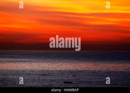 Lone Fisherman boat on the sea at sunrise, São Conrado Bech, Rio de Janeiro, Brazil - Stock Photo