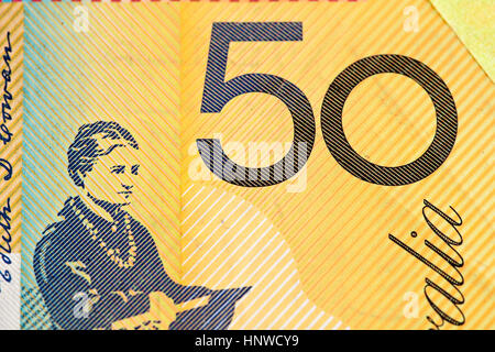 Australian 50 dollar bill fragment closeup showing the number fifty on yellow background - Stock Photo