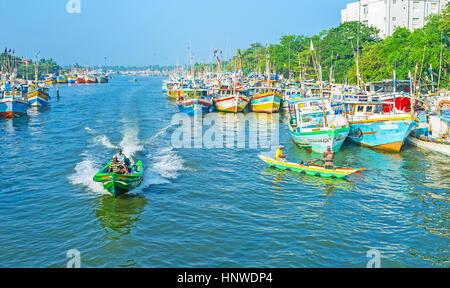 NEGOMBO, SRI LANKA - NOVEMBER 25, 2016: The boats sailing in lagoon, occupied with numerous fishing trawlers, on - Stock Photo