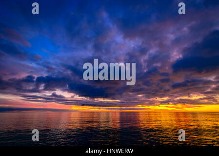 Colorful dramatic sunset view above Glenelg Beach viewed from jetty, South Australia - Stock Photo