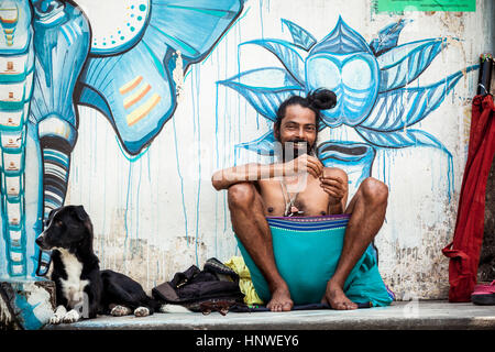 Rishikesh, India - September 22, 2014: Young pilgrim with dog sits near the wall painted with street art in Rishikesh, - Stock Photo