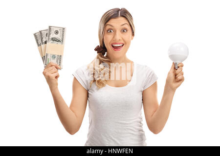 Delighted woman holding bundles of money and a LED light bulb isolated on white background - Stock Photo
