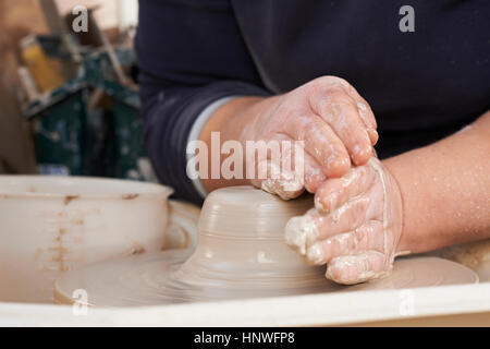 Close Up Of Potter Moulding Clay On Wheel - Stock Photo