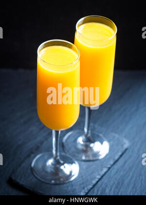 Freshly squeezed orange juice in champagne glasses. - Stock Photo