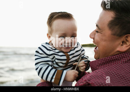 Father on beach holding smiling baby boy - Stock Photo