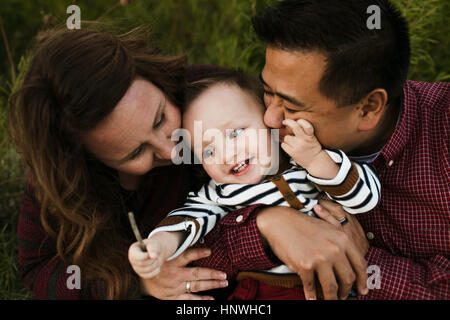 Mother and father hugging smiling baby boy - Stock Photo