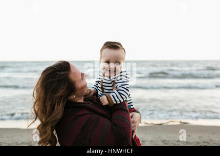 Mother on beach holding smiling baby boy - Stock Photo