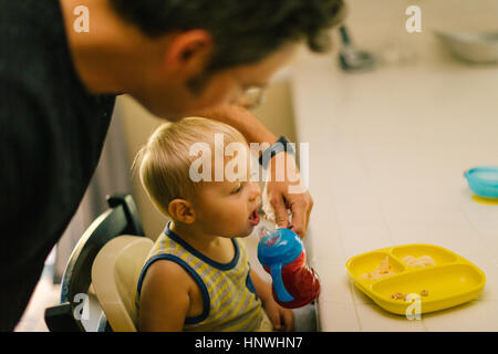 Father helping young son at meal time - Stock Photo