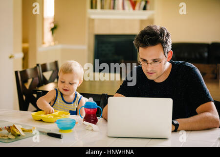 Father and young son sitting at table, son eating, father using laptop - Stock Photo