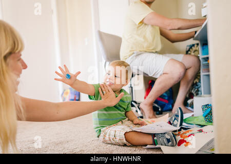 Father using computer whilst young son plays on floor with mother - Stock Photo