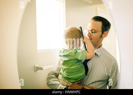 Father holding young son, son combing hair, reflected in mirror - Stock Photo