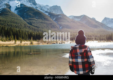 Young boy beside river, rear view, Three Sisters, Rocky Mountains, Canmore, Alberta, Canada